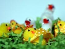 Weißes und gelbes Plüschostern-Huhn erscheint im grünen Nest Stockbilder