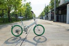Weißes und grünes Fahrrad im Dorf Lizenzfreie Stockfotografie