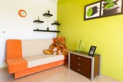 Weißes und grünes Schlafzimmer mit orange Sofa Stockbild
