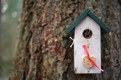 Weißes und grünes Vogelhaus mit dem hängenden Herzen gemacht von den Samen Lizenzfreies Stockbild