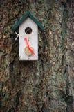 Weißes und grünes Vogelhaus mit dem hängenden Herzen gemacht von den Samen stockbilder