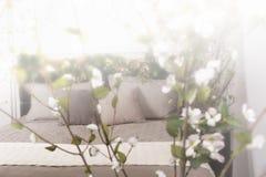Weißes und graues gemütliches Schlafzimmer mit Blumen auf dem Bettgestell Lizenzfreies Stockfoto