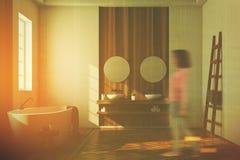 Weißes und hölzernes Badezimmer, weiße Wanne, Spiegel, Mädchen Lizenzfreie Stockfotografie