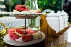 Weißes und rosa Macaron auf cakestand gegen Behälterhintergrund Lizenzfreie Stockfotografie