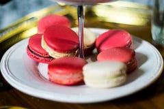 Weißes und rosa Macaron auf cakestand mit Behälter auf Warenkorb Stockbilder