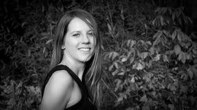 Weißes und schwarzes Porträt der recht schönen jungen Frau mit reizend Lächeln und dem langen Haar im Park während eines Tages Lizenzfreie Stockfotografie