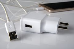 Weißes USB-Telefonladegerät mit Telefon im Hintergrund Lizenzfreies Stockbild