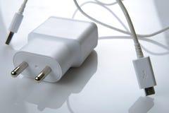 Weißes USB-Telefonladegerät mit Telefon im Hintergrund Lizenzfreie Stockbilder