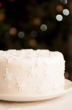 Weißes Weihnachtskuchen abgedeckt in den Schneeflocken Stockfotos