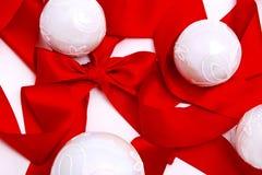 Weißes Weihnachtskugeln auf rotem Farbband Stockbild