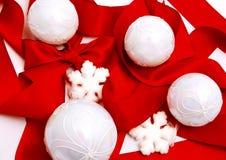 Weißes Weihnachtskugeln und rotes Farbband Stockfotos