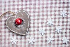 Weißes Weihnachtsschneeflocken und hölzerne Herzdekoration auf kariertem rosa Hintergrund Weinlesewintertapete Beschneidungspfad  Stockfotografie