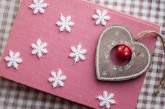 Weißes Weihnachtsschneeflocken und hölzerne Herzdekoration auf rosa Hintergrund Wintertapete Beschneidungspfad eingeschlossen Lizenzfreie Stockfotografie