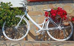 Weißes Weinlesefahrrad verziert mit roten Blumen Stockfotografie