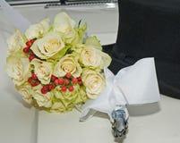 Weißes Weinlesehochzeitsauto, der Blumenstrauß der Braut und der schwarze Hut des Mannes Lizenzfreie Stockfotografie