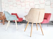 Weißes Wohnzimmer mit bunten roten, gewachsenen, blauen Stühlen, kleiner Tabelle und weißen gelben roten Details kopieren grafisc Lizenzfreie Stockfotos