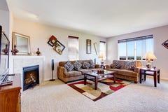 Weißes Wohnzimmer mit Kamin und bunter Wolldecke Stockbilder
