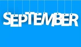 Weißes Wort SEPTEMBER - fassen Sie das Hängen an den Seilen auf blauem Hintergrund ab Stockfotos
