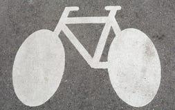 Weißes Zeichen des Fahrrades, auf Beton Lizenzfreies Stockfoto