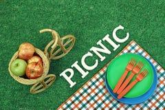 Weißes Zeichen-Picknick auf Rasen, Platten und Weidenfahrrad-Korb Stockbild