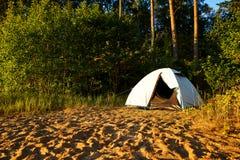 Weißes Zelt, das an einer kampierenden Stelle des Strandes am See Vänern in Schweden steht Die Sonne ist glänzend und bald wird  Stockfotografie