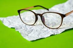 Weißes zerknittertes Papier und Grünbuch augenglas stockfotos