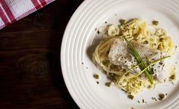 Weißfisch auf Teigwaren mit Petersilie und Schnittlauchen stockfotos