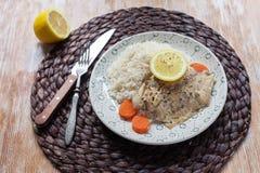 Weißfisch diente am Tisch mit Zitrone und Reis Lizenzfreie Stockbilder