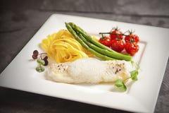 Weißfisch mit Schaum, Bandnudeln und grünem Spargel Lizenzfreie Stockfotos