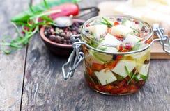 Weißkäsewürfel und -kräuter tauchten in Olivenöl in kleinem Glas O ein Stockfotos