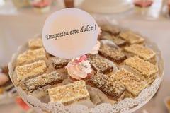 Weißmetallbehälter mit Quadratkuchen und einem kleinen Kuchen mit der Mitteilung in rumänischem dulce ` Dragostea e `, ` Liebe üb stockfoto