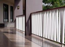 Weißmetallzaun auf ruhiger minimaler Urlaubshotelkorridorweise zu den Räumen mit Schatten und Reflexionen Stockfotografie