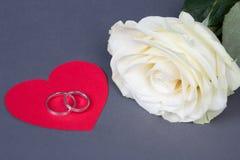 Weißrosenblume und -Eheringe auf rotem Herzen über Grau Stockfotografie