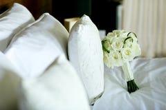 Weißrosenblumen-Hochzeitsblumenstrauß auf Bett Stockfotos