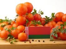Weißrussland-Flagge auf einer Holzverkleidung mit den Tomaten lokalisiert auf einem Weiß Lizenzfreies Stockfoto