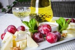 Weißwein mit einem Käse und Trauben Lizenzfreie Stockbilder
