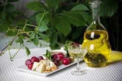 Weißwein und Käse auf dem Tisch Stockbild