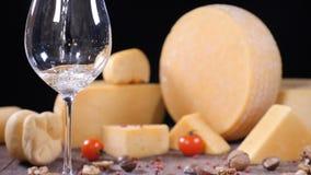 Weißwein wird in ein Glas mit einem varieyty des Hartkäses auf Hintergrund gegossen Lebensmittelkunstkonzept Restaurantumhüllung stock video footage