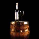 Weißweinflasche und -glas auf einem hölzernen Fass - lokalisiert auf Schwarzem Stockbilder
