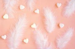 Weiße Federn und weiße Herzen auf einem leichten Hintergrund die Farbe der Livekoralle Hintergrund lizenzfreies stockfoto