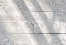Weiße hölzerne schäbige rustikale verwitterte Schreibtischplanken mit gebrochener Farbe des Sonnenlichts stockfotografie