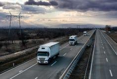 Weiße Lastwagen-LKWs des Wohnwagens oder des Konvois auf Landlandstraße lizenzfreie stockbilder