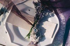 Weiße Platte, Gabel, Gastkarte und Lavendel Boutonniere lizenzfreies stockbild