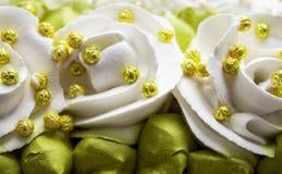 Weiße Rosen und grüne Blätter machten mit Sahne, Nahaufnahme lizenzfreie stockfotografie