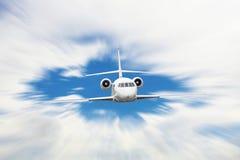 Weißes Flugzeug mit Bewegungsunschärfeeffekt fliegt über Wolken stockfotografie