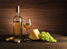 Weißweinflasche und -glas auf hölzernem Hintergrund lizenzfreie stockfotos