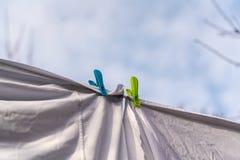 Wei?e Kleidung hing heraus, um auf einer waschenden Linie zu trocknen und befestigt durch die Kleiderhaken gegen den blauen Himme lizenzfreie stockfotografie