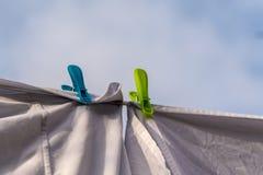 Wei?e Kleidung hing heraus, um auf einer waschenden Linie zu trocknen und befestigt durch die Kleiderhaken gegen den blauen Himme lizenzfreie stockbilder