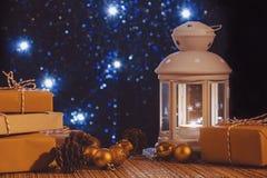 Wei?e Laterne mit einer brennenden Kerze und K?sten mit Geschenken auf dem Hintergrund des Weihnachtsbaums mit Lichtern Sch?n lizenzfreie stockbilder