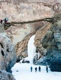 Wei?er gefrorener Wasserfall zwischen Bergen Leutetrekking H?lzerne Br?cke Zanskar-Fluss Leh Ladakh Indien stockfoto